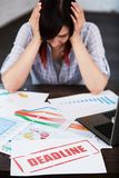 Stressed woman in office thinking about deadline. Royalty Free Stock Images