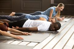 Tired diverse people relaxing on mats after yoga stretching trai. Tired diverse african and caucasian people relaxing smiling having fun lying on mat floor at stock photography