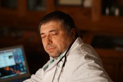 Tired doctor resting. Exhausted overworked doctor sitting at his desk with closed eyes Royalty Free Stock Image