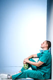 Tired doctor sitting after surgery in a hospital corridor. stock photography