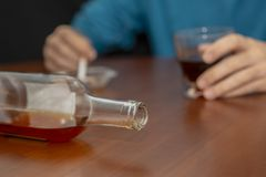 Close-up of a bottle and background man drinking and smoking. Tired drunken man on the table at home. Alcohol addiction Royalty Free Stock Image