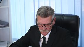 Tired old businessman working with a computer in a modern office stock footage