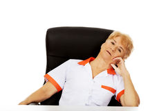 Tired elderly female doctor or nurse sitting behind the desk Royalty Free Stock Images