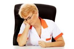 Tired elderly female doctor or nurse sleep with head on hand Stock Image