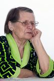 The tired elderly woman. Sits at a table Royalty Free Stock Photo