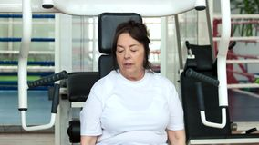 Tired elderly woman at gym. Senior woman wiping with towel after hard sport training on gym equipment. Sport and age stock video footage