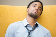 Tired employee. Closeup portrait, young disturbed, distressed employee in blue shirt striped tie, exhausted, resting head on seat, worried about something, about Stock Photos