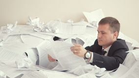 A tired employee is sitting in a pile of papers. Problems with the work of the employee. A young man in an office suit. A tired employee is sitting in a pile of stock video footage