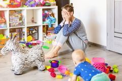 Tired of everyday household mother sitting on floor with hands on face. Kid playing in messy room. Scaterred toys and
