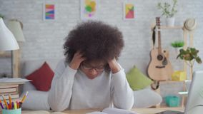 Tired and exhausted african american students woman with an afro hairstyle. At home stock footage