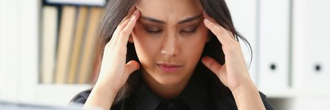 Tired and exhausted woman looks at documents propping up her head with her hands royalty free stock photography