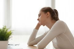 Tired exhausted woman sitting at desk falling asleep, working too long. Tired exhausted female employee or student sitting at desk falling asleep, working too royalty free stock photos