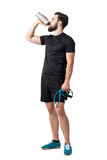 Tired exhausted fitness trainer holding resistance bands drinking smoothie. Full body length isolated over white studio background Stock Images