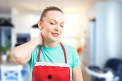 Tired and exhausted housekeeper or maid grabbing scruff Royalty Free Stock Photography