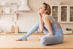 Languid blonde young woman resting on kitchen table stock image