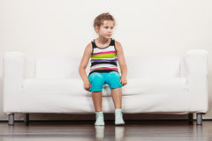 Tired exhausted lazy little girl kid sits on sofa Royalty Free Stock Image
