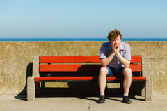Tired exhausted man sitting on bench by sea ocean. Royalty Free Stock Photos
