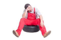 Tired and exhausted mechanic sitting on a car wheel Stock Photography
