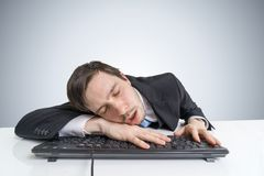 Tired or exhausted overworked businessman is sleeping on keyboard Stock Image