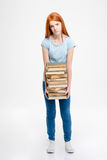 Tired exhausted woman standing and holding stack of books Royalty Free Stock Images