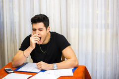 Tired, exhausted young man yawning while working. Or studying at home sitting at table with paper sheets in front of him Royalty Free Stock Images