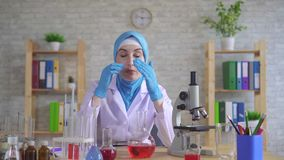 Tired exhausted young muslim woman scientist chemist in national scarf working in the lab. Tired exhausted young muslim woman scientist chemist in glasses in stock footage