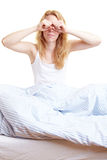 Tired eyes. Woman rubbing her eyes after waking up royalty free stock image