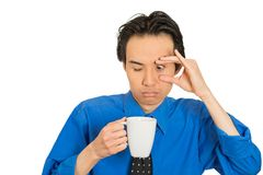 Tired falling asleep young businessman holding cup of coffee royalty free stock images