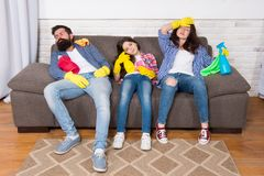 Tired family. exhausted family after cleaning house. tired family hold cleaning products. Mother, father and daughter royalty free stock photos