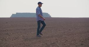 Tired farmer stretching while walking in farm stock footage