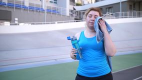 Tired fat female drinking water after workout