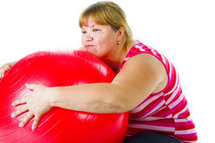 Tired fat woman. With big red gymnastic ball Royalty Free Stock Photography