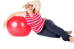 Tired fat woman. With big red gymnastic ball royalty free stock photo