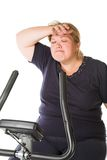 Tired fat woman. Training on the bike Stock Images