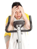 Tired fat woman on  fitness bicycle Royalty Free Stock Photos