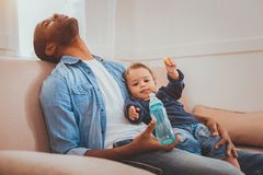 Tired father babysitting his child and sleeping. Exhausted. Exhausted afro-american daddy sleeping while babysitting his little son royalty free stock photo