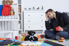 Tired father sitting on floor. Among baby toys Royalty Free Stock Images