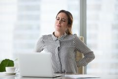 Tired fatigued businesswoman worker rubbing back feeling lower lumbar pain
