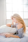 Tired fatigued woman lying on bed having a headache. Tired fatigued woman with beautiful long blonde hair lying on bed having a headache royalty free stock images