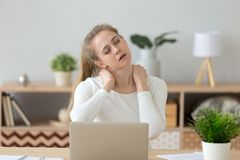Tired fatigued young woman massaging stiff neck rubbing tensed muscles. Hurt to relieve back joint shoulder fibromyalgia pain after long sedentary computer work stock photos
