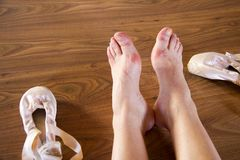 Tired feet of ballerina sitting on a wooden floor near her used pointe shoes stock photos