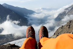 Tired feet of the climber in the shoes on mountains. Royalty Free Stock Images