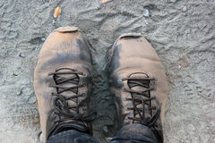 Tired feet in dusty boots. A pair of boots after a long walk on dusty roads Stock Photography
