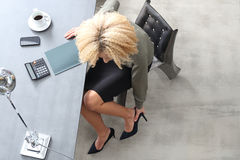 Tired feet in high heels. Woman massaging feet while sitting at her desk royalty free stock photo