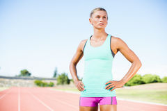 Tired female athlete standing on running track Royalty Free Stock Image