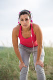Tired female athlete taking an exercising break Royalty Free Stock Photos