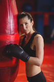 Tired female boxer leaning on punching bag Stock Photography