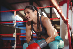 Tired female boxer sitting in the ring Royalty Free Stock Images