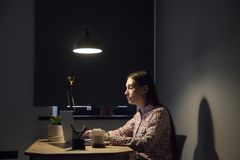 Tired female browsing information at laptop working late hours stock image