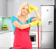 Tired female cleaner after cleaning a kitchen Royalty Free Stock Photography